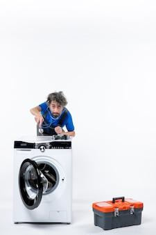 Vorderansicht des mechanikers, der das stethoskop über die waschmaschine auf die weiße wand legt