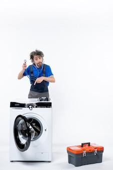 Vorderansicht des mechanikers, der ein stethoskop hält und auf die waschmaschine an der weißen wand zeigt