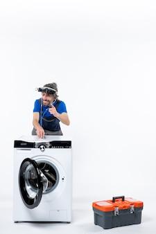 Vorderansicht des mechanikers mit kopflaterne, der das stethoskop auf die waschmaschine auf die weiße, isolierte wand legt