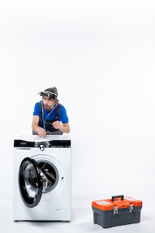 Vorderansicht des mechanikers mit kopflaterne mit stethoskop, das hinter der waschmaschine an der weißen wand steht