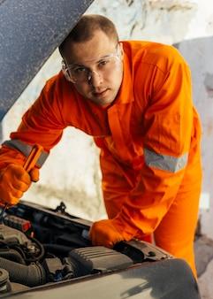 Vorderansicht des mechanikers mit schutzbrille und uniform