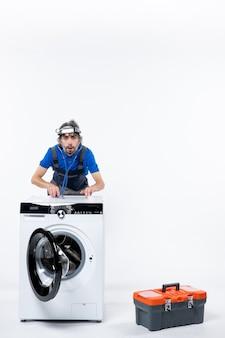 Vorderansicht des mechanikers mit stirnlampe mit stethoskop, das hinter der waschmaschine an der weißen wand steht