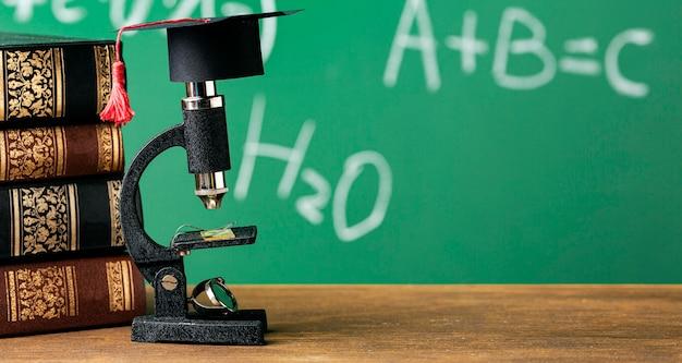 Vorderansicht des mikroskops mit akademischer kappe und kopierraum