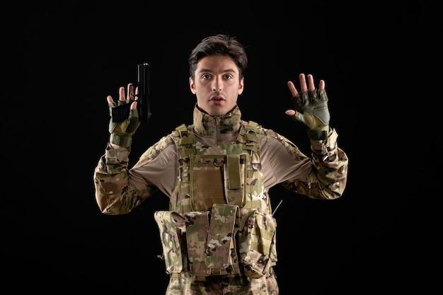Vorderansicht des militärs in uniform, der sich mit pistole an schwarzer wand ergibt