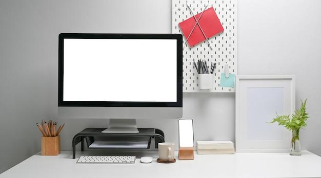 Vorderansicht des mock-up-computers mit leerem bildschirm, smartphone und bürobedarf auf weißem schreibtisch im home-office-interieur.