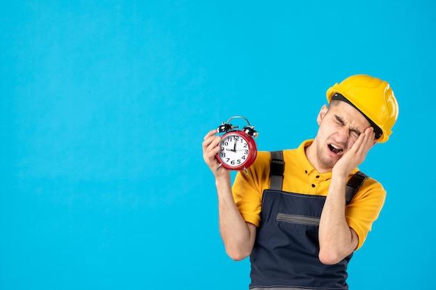 Vorderansicht des müden männlichen arbeiters in der gelben uniform mit den uhren auf blau