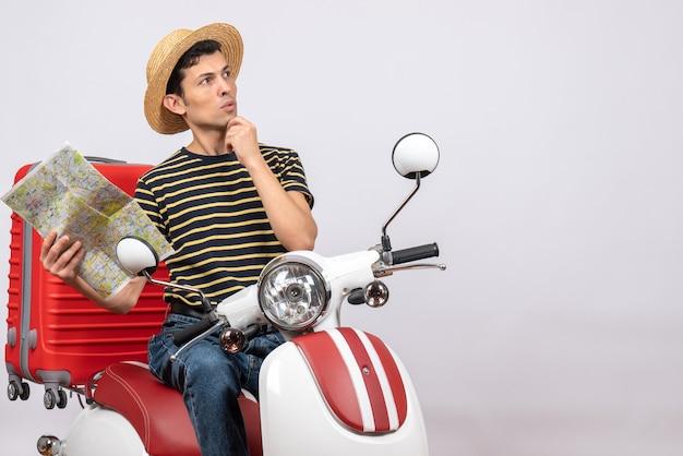 Vorderansicht des nachdenklichen jungen mannes mit strohhut auf moped, das karte hält