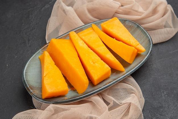Vorderansicht des natürlichen frischen gelben käses auf einem halb gefalteten handtuch auf schwarzem hintergrund