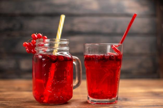 Vorderansicht des natürlichen organischen frischen johannisbeersaftes in einem glas und einer flasche, die mit röhren auf einem holztisch serviert wird