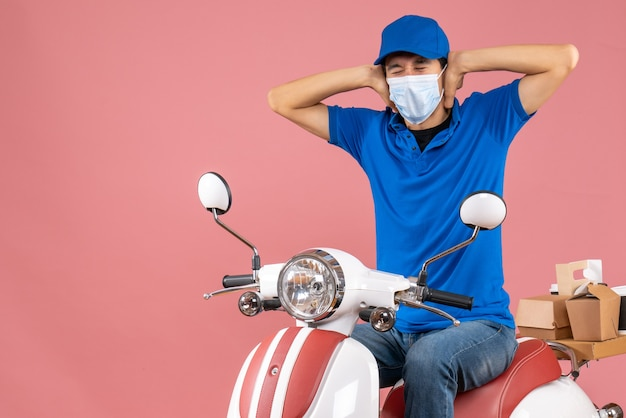 Vorderansicht des nervösen emotionalen liefertyps in medizinischer maske mit hut, der auf einem roller auf pastellfarbenem pfirsichhintergrund sitzt
