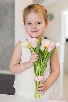 Vorderansicht des netten kleinen mädchens, das tulpe hält, blüht bündel