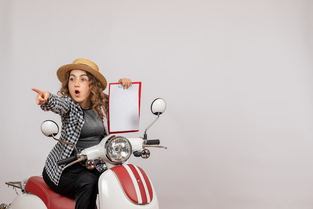 Vorderansicht des neugierigen jungen mädchens auf moped, das klemmbrett auf grauer wand hält