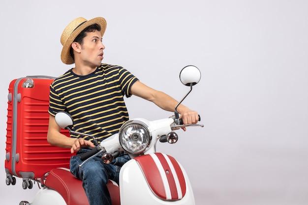 Vorderansicht des neugierigen jungen mannes mit strohhut auf moped, der auf etwas starrt