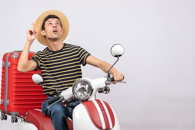 Vorderansicht des neugierigen jungen mannes mit strohhut auf moped, der oben schaut