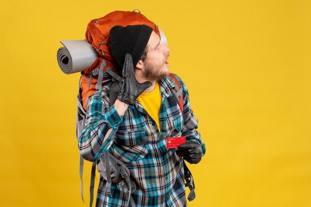 Vorderansicht des neugierigen jungen rucksacktouristen mit dem schwarzen hut, der kreditkarte hält, die etwas hört
