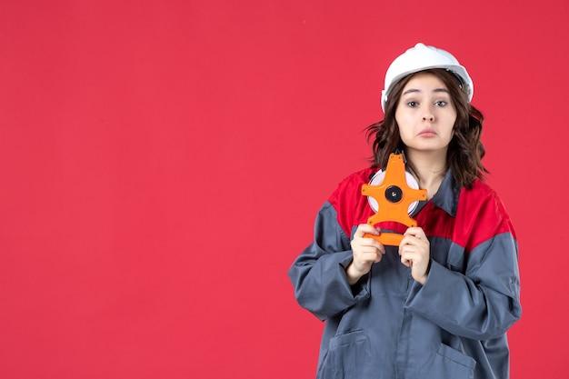 Vorderansicht des neugierigen weiblichen architekten in uniform mit schutzhelm, der maßband auf isolierter roter wand hält