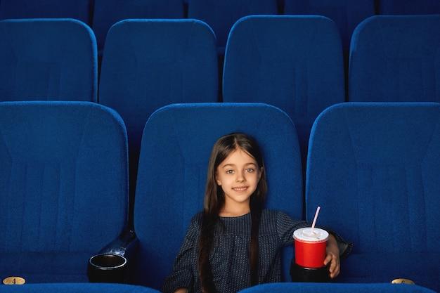 Vorderansicht des niedlichen brünetten weiblichen kindes, das kamera betrachtet und lächelt, während film im kino genießt