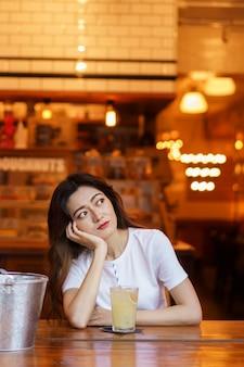 Vorderansicht des niedlichen japanischen mädchens, das limonade trinkt