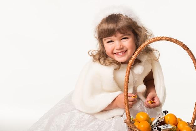 Vorderansicht des niedlichen kindes, das neben korb steht und zitrusfrüchte hält.