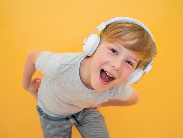 Vorderansicht des niedlichen kleinen jungen, der musik hört