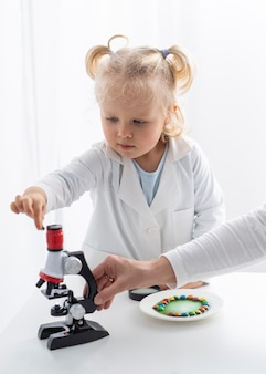 Vorderansicht des niedlichen kleinkindes, das über wissenschaft mit mikroskop lernt