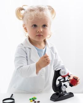 Vorderansicht des niedlichen kleinkindes mit laborkittel und mikroskop