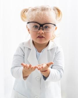 Vorderansicht des niedlichen kleinkindes mit laborkittel und schutzbrille