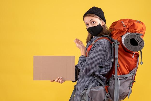 Vorderansicht des niedlichen reisenden mädchens mit schwarzer maske und rucksack, die pappe halten