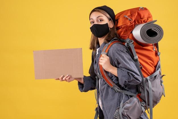 Vorderansicht des niedlichen weiblichen reisenden mit der schwarzen maske und dem rucksack, der karton hält