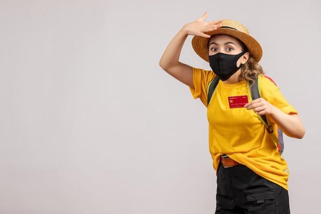 Vorderansicht des niedlichen weiblichen reisenden mit rucksack, der karte auf grauer wand hält