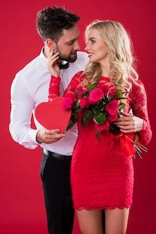 Vorderansicht des paares, das valentinstagsymbole hält