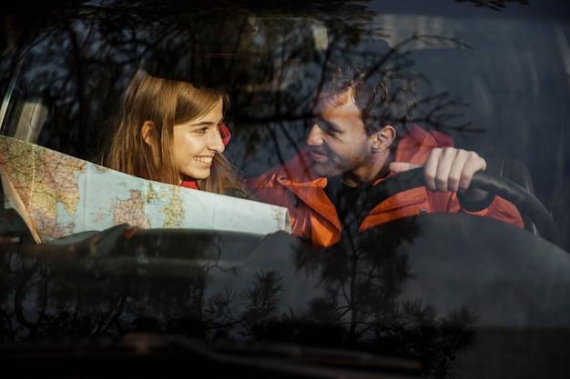 Vorderansicht des paares mit karte innerhalb des autos, das auf einer straßenreise geht