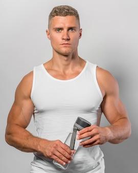 Vorderansicht des passenden mannes, der wasserflasche hält