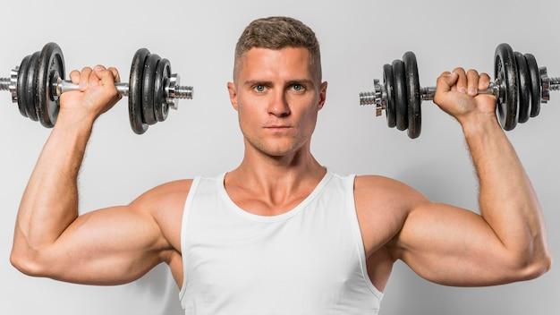 Vorderansicht des passenden mannes mit tankoberteil, der gewichte hält