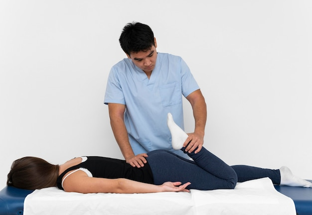 Vorderansicht des physiotherapeuten, der beinübungen mit frau macht