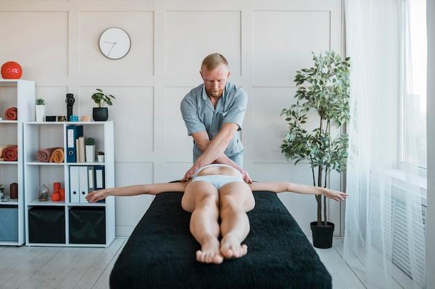 Vorderansicht des physiotherapeuten, der übungen an patientin durchführt