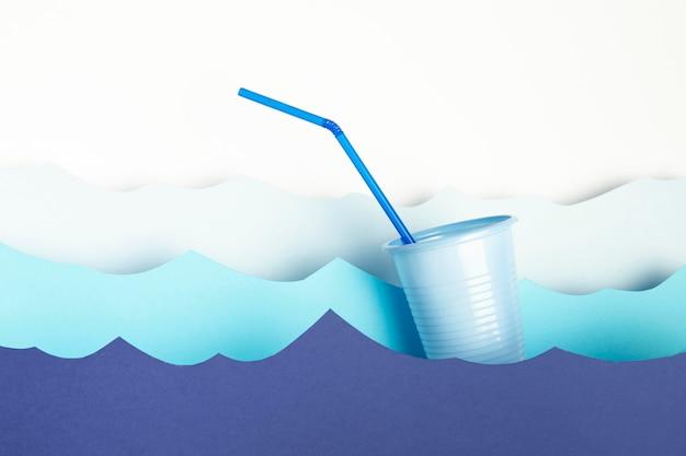 Vorderansicht des plastikbechers mit stroh- und papierwellen