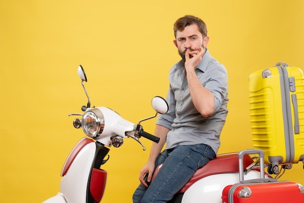 Vorderansicht des reisekonzepts mit dem bärtigen jungen mann, der auf motorrad mit koffern sitzt, die perfekte geste auf ihm auf gelb machen