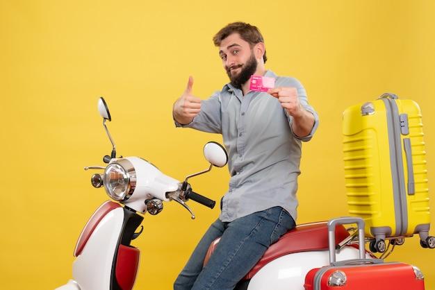Vorderansicht des reisekonzepts mit dem glücklichen lächelnden jungen mann, der auf motorrad mit koffern auf ihm sitzt, die bankkarte auf gelb halten