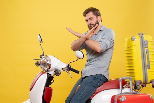 Vorderansicht des reisekonzepts mit dem jungen mann, der auf motorrad mit koffern sitzt, die stoppgeste auf es auf gelb machen