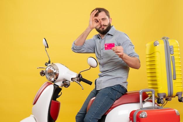 Vorderansicht des reisekonzepts mit dem jungen selbstbewussten bärtigen mann, der auf motorrad sitzt, das bankkarte zeigt, die brillen gestikulieren auf es auf gelb