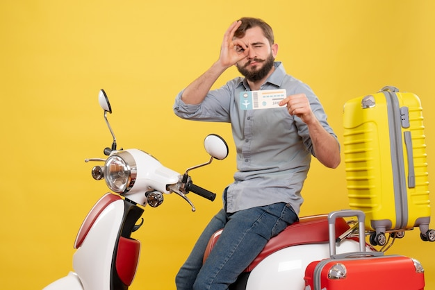 Vorderansicht des reisekonzepts mit dem jungen selbstbewussten bärtigen mann, der auf motorrad sitzt, das ticket macht, das brillengestik auf es auf gelb macht
