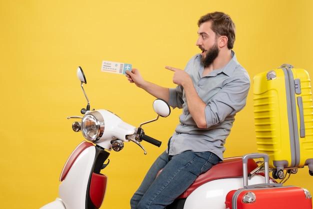 Vorderansicht des reisekonzepts mit dem jungen überraschten bärtigen mann, der auf dem motorrad sitzt, das ticket auf es auf gelb zeigt