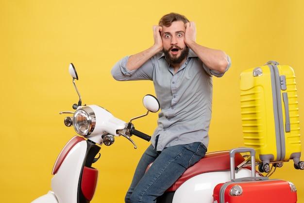 Vorderansicht des reisekonzepts mit dem jungen verängstigten bärtigen mann, der auf motorrad auf ihm auf gelb sitzt