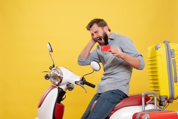 Vorderansicht des reisekonzepts mit dem nervösen jungen mann, der auf motorrad mit koffern auf ihm sitzt, die bankkarte auf gelb halten
