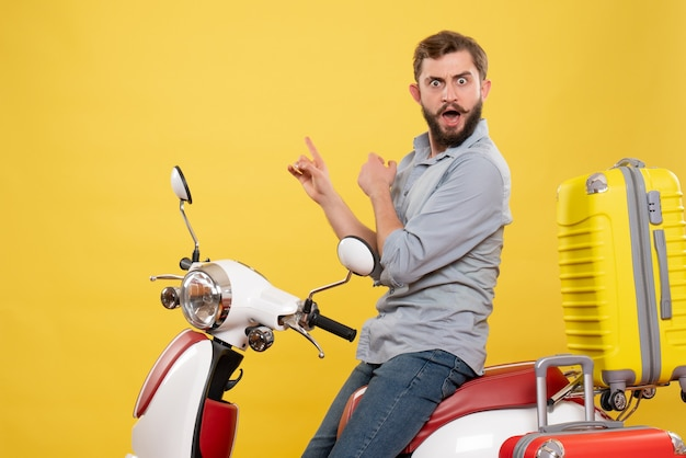 Vorderansicht des reisekonzepts mit dem nervösen verärgerten emotionalen jungen mann, der auf motorrad mit koffern auf ihm auf gelb sitzt