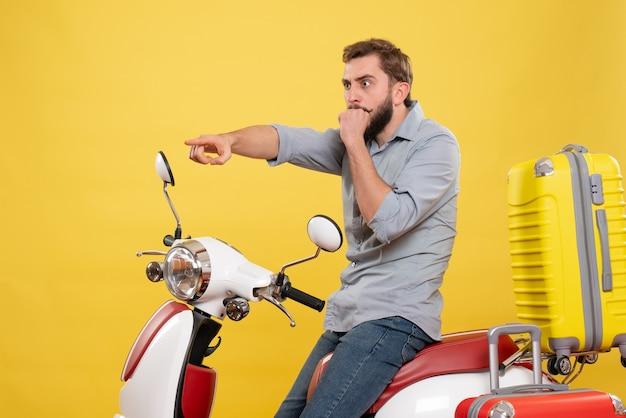 Vorderansicht des reisekonzepts mit dem schockierten jungen mann, der auf motorrad mit koffern sitzt, die auf auf gelb nach vorne zeigen