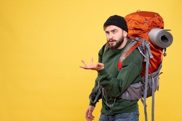 Vorderansicht des reisekonzepts mit dem sich wundernden emotionalen jungen mann mit packpack