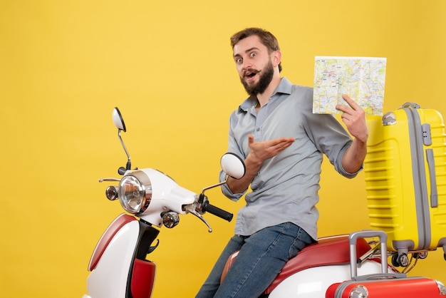 Vorderansicht des reisekonzepts mit dem sich wundernden jungen mann, der auf motorrad mit koffern darauf zeigt, die zurückhaltende karte auf gelb zeigen