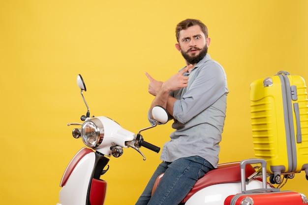 Vorderansicht des reisekonzepts mit dem sich wundernden neugierigen emotionalen jungen mann, der auf motorrad mit koffern auf ihm auf gelb sitzt